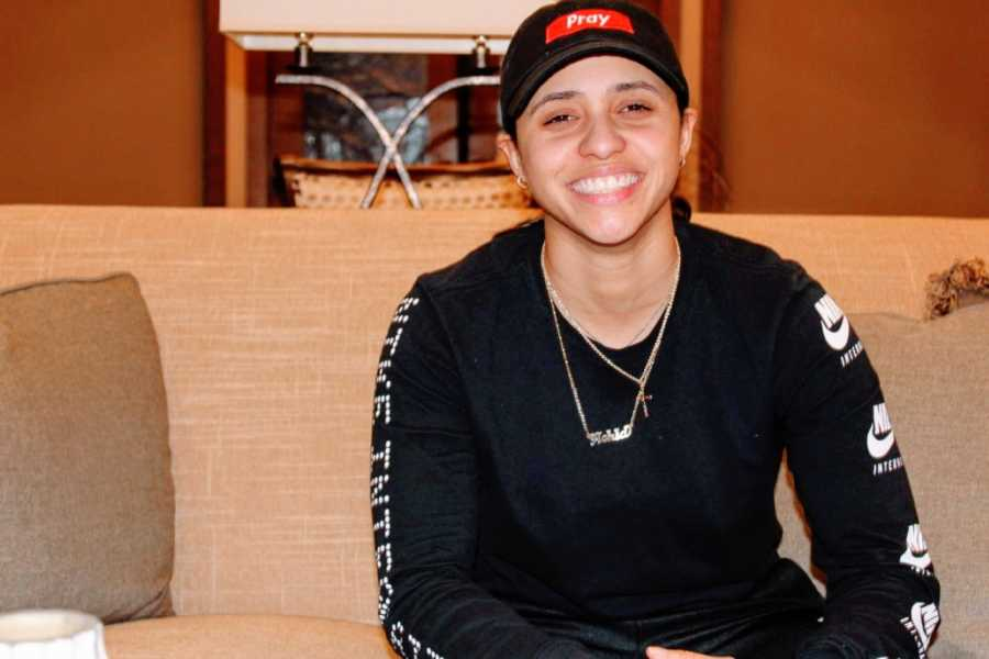 Young lesbian smiles for the camera dressed in masculine clothing and a baseball cap that says 'pray'