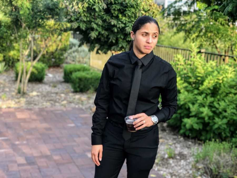 Woman looks serious in photo, wearing all-black suit and holding a drink
