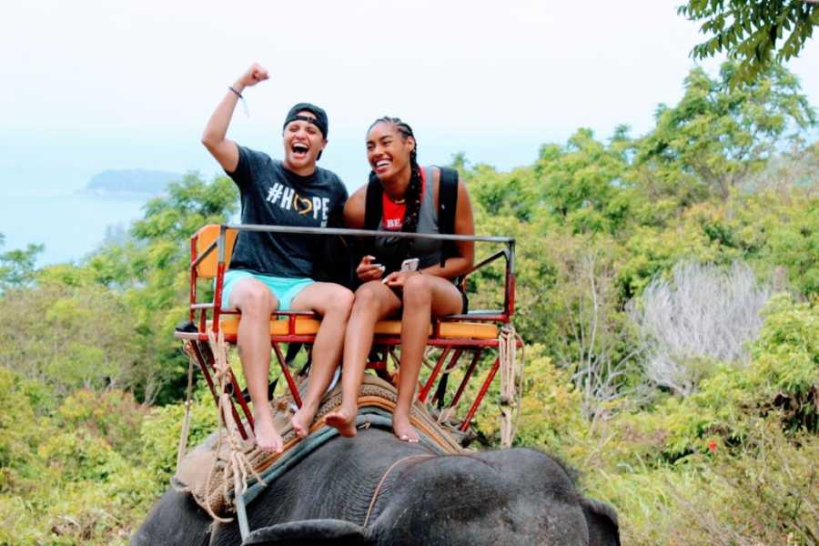 Lesbian woman cheers while riding an elephant with her wife