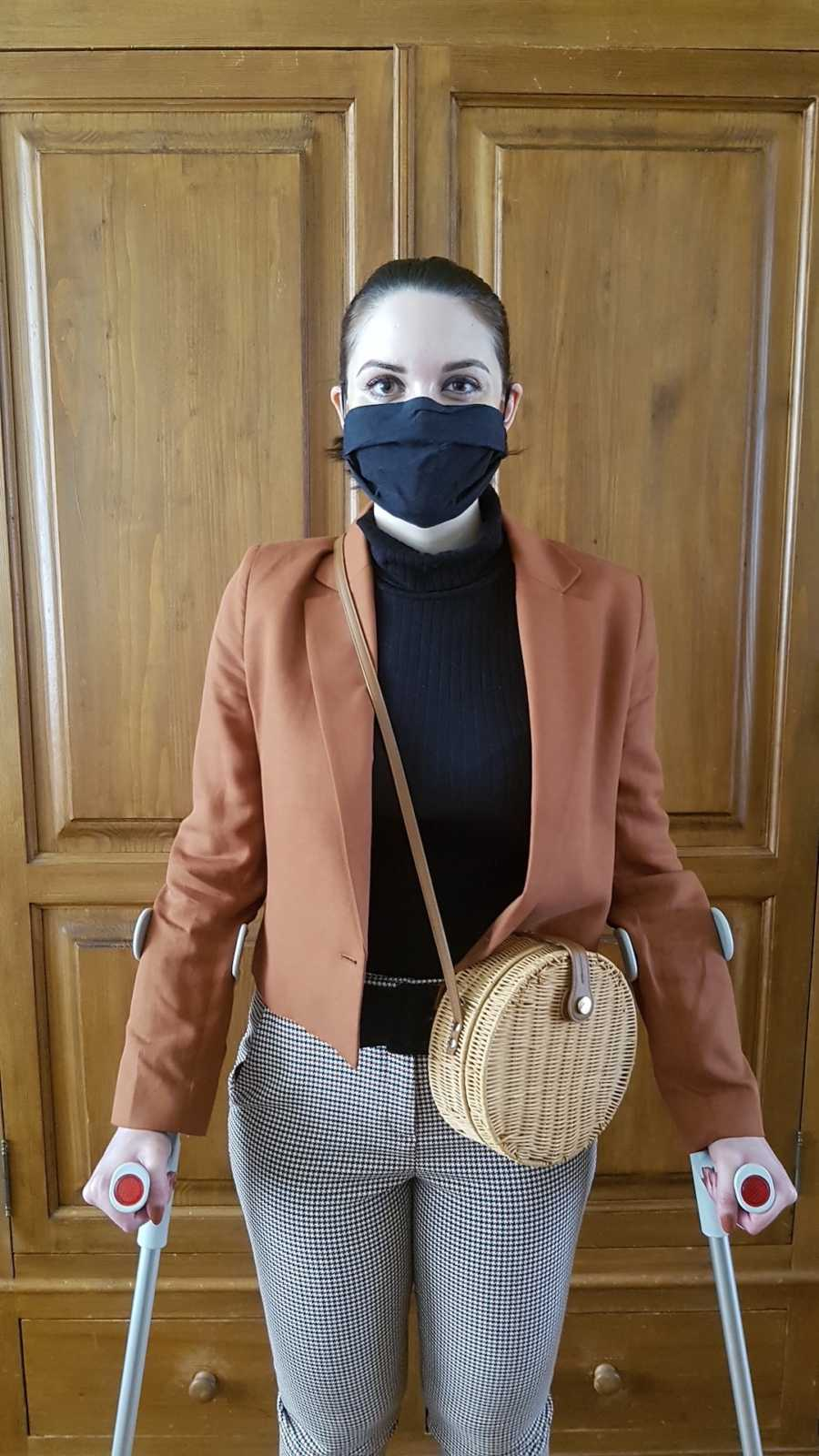 woman with arm crutches wearing a mask
