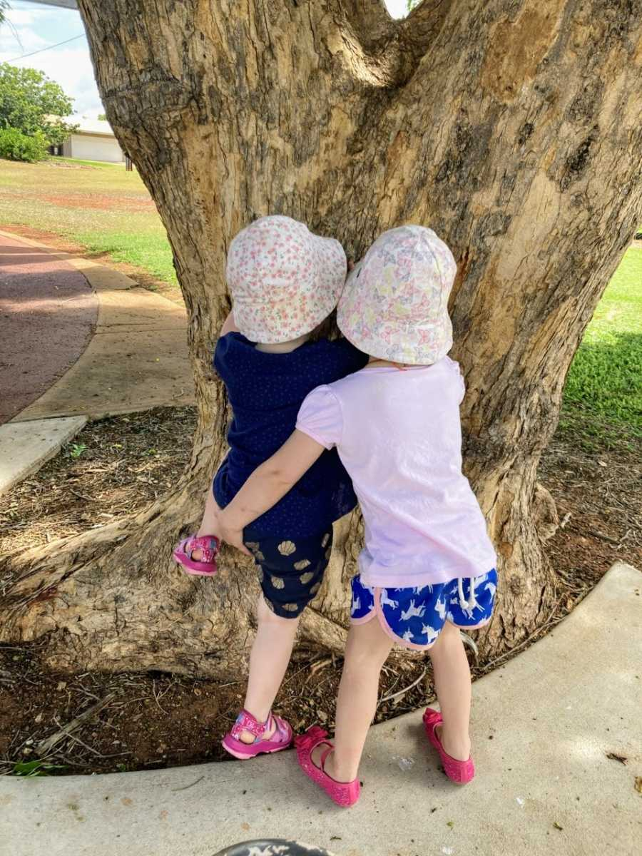 Mom snaps photo of twin sisters helping each other climb up a tree