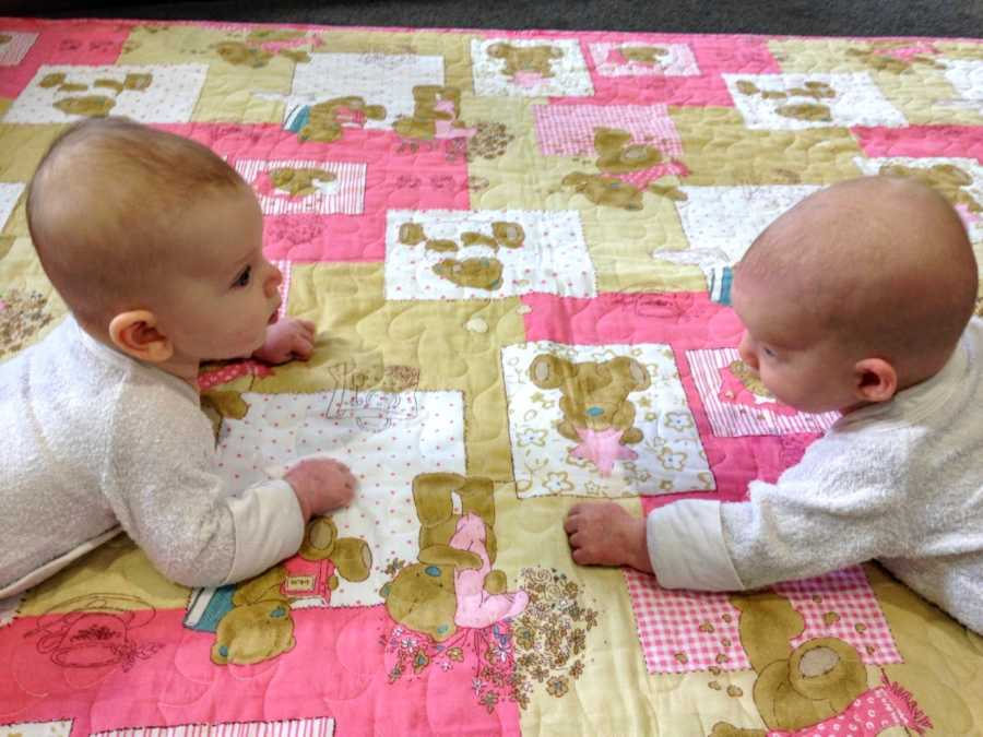 Mom snaps photo of twin daughters learning to crawl and hold their heads up during tummy time