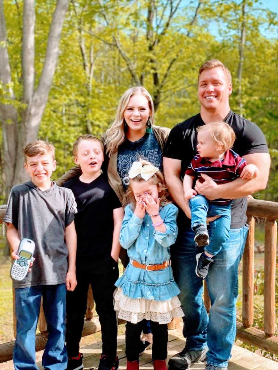Young family of six take a candid family photo together on the back porch of their dream home