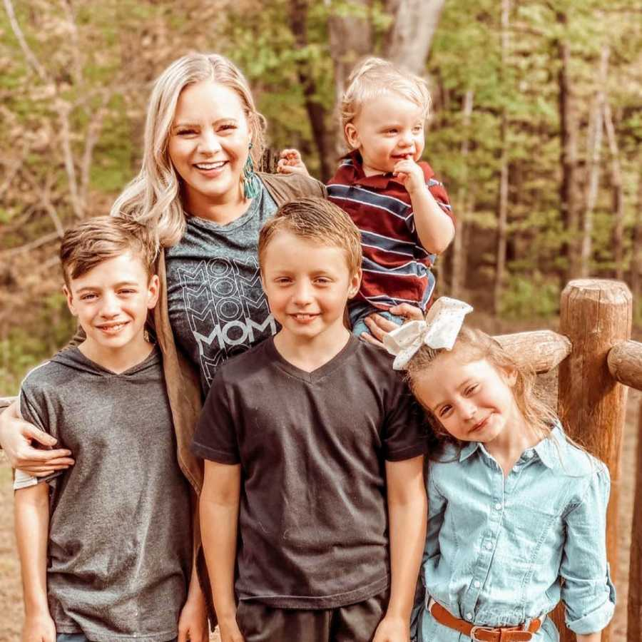 Young mom of four takes a photo with her kids on the back porch of her dream home