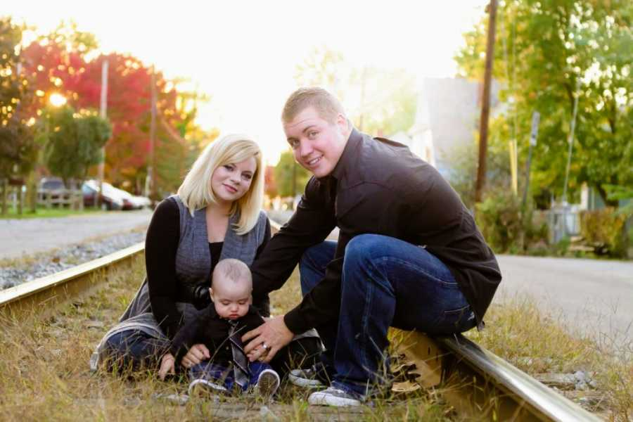 Young Christian married couple take photos on railroad tracks with their infant son