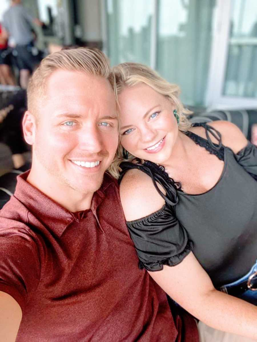 Young married couple advocating for postpartum depression awareness take a selfie together while sitting on a balcony