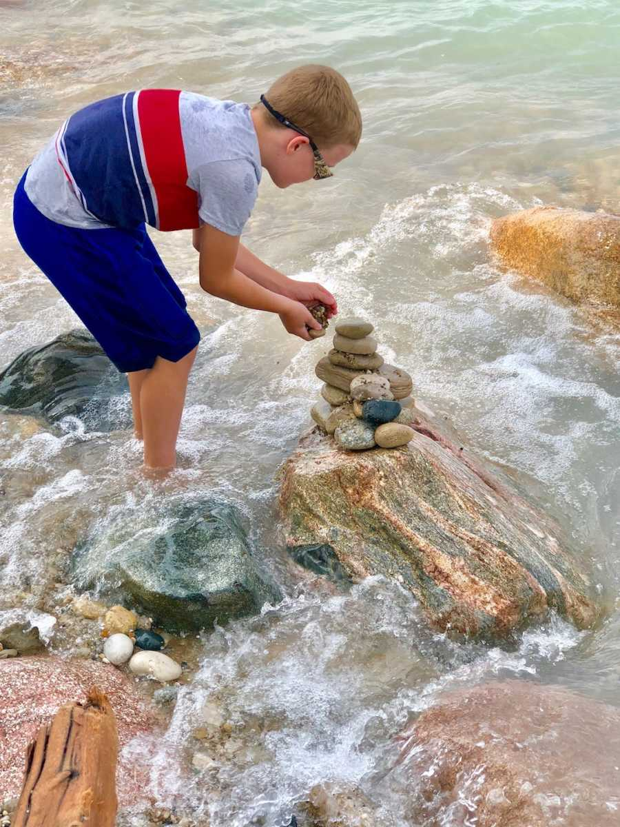 boy stacking rocks at the beach
