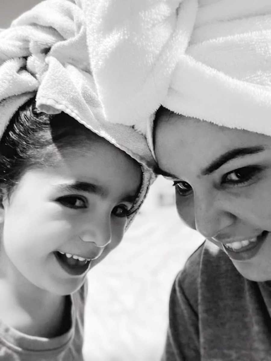 Mom takes a selfie with her daughter with their hair wrapped up in towels