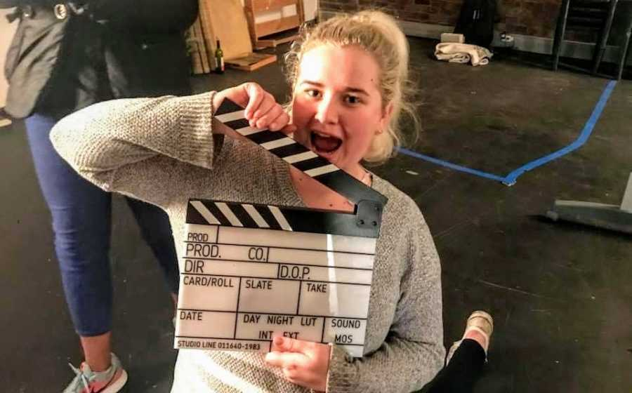 A young woman at university with a clapboard
