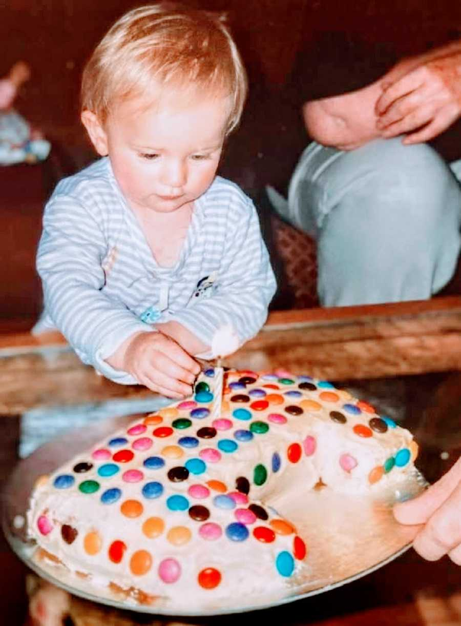 A little girl sitting by a birthday cake