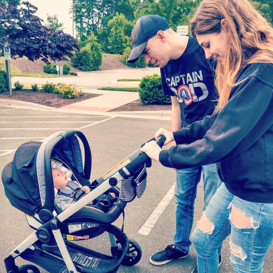 First time parents stare at their newborn son while he lays in his stroller during a family walk
