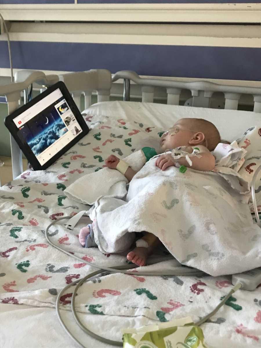 baby watching a tv under blanket