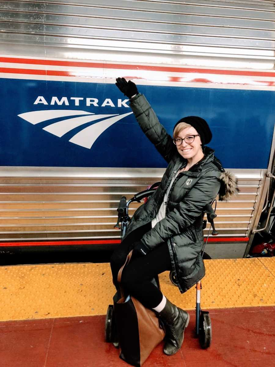 College student sits on her walker and takes a photo in front of an Amtrack train