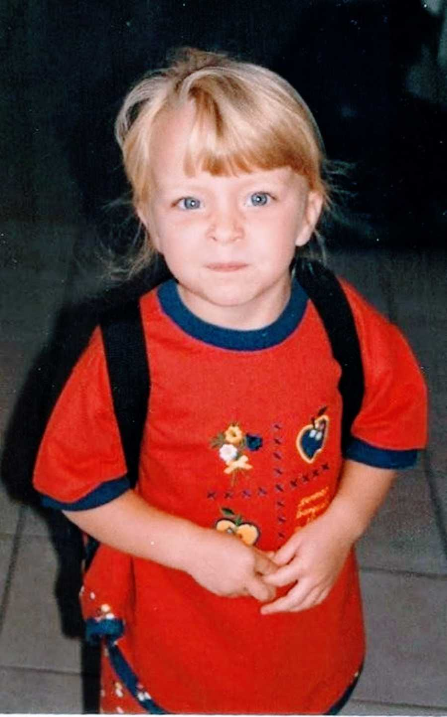 Young girl with blonde hair and blue eyes makes a silly tough face at the camera