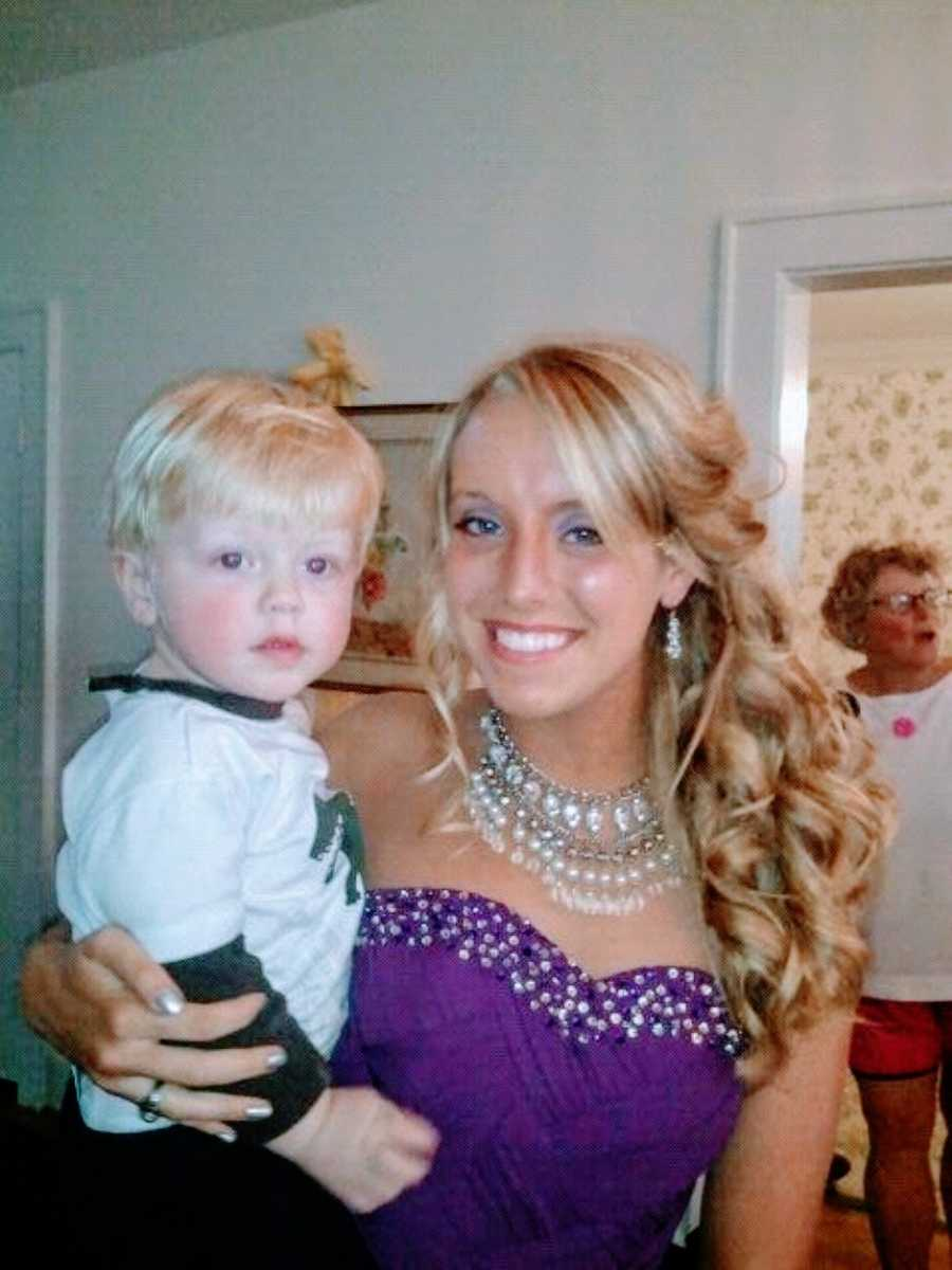 Teen girl holds her baby brother while getting ready for Homecoming in purple dress