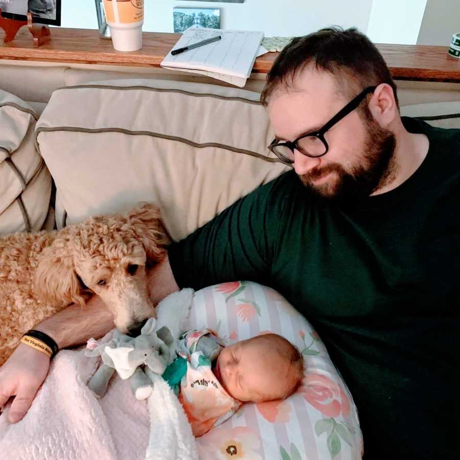 New dad takes photo with his newborn daughter and beloved family dog all cuddling on the couch together