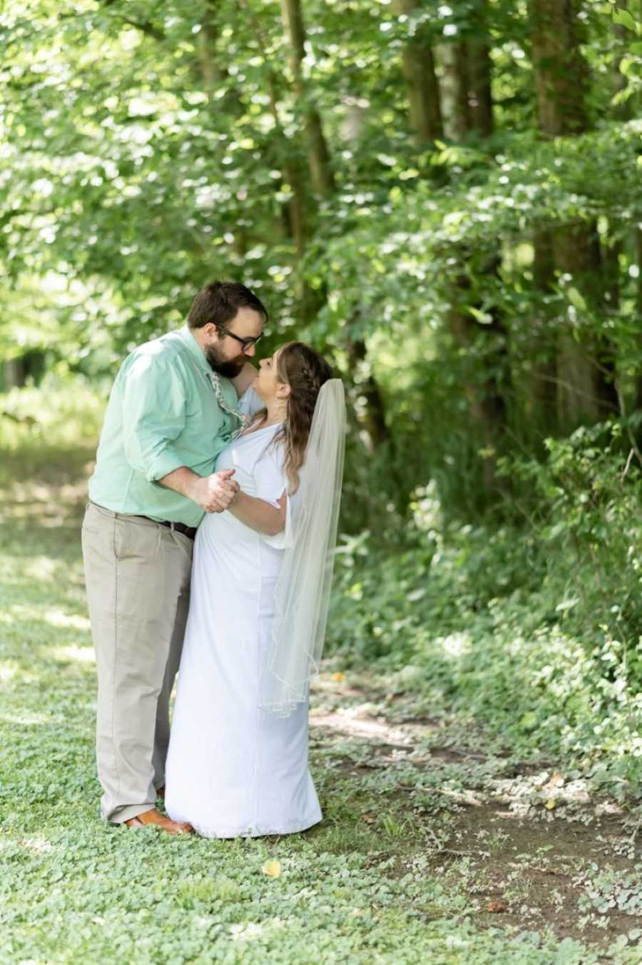 Newly weds share a sweet, intimate moment outside during their wedding photos