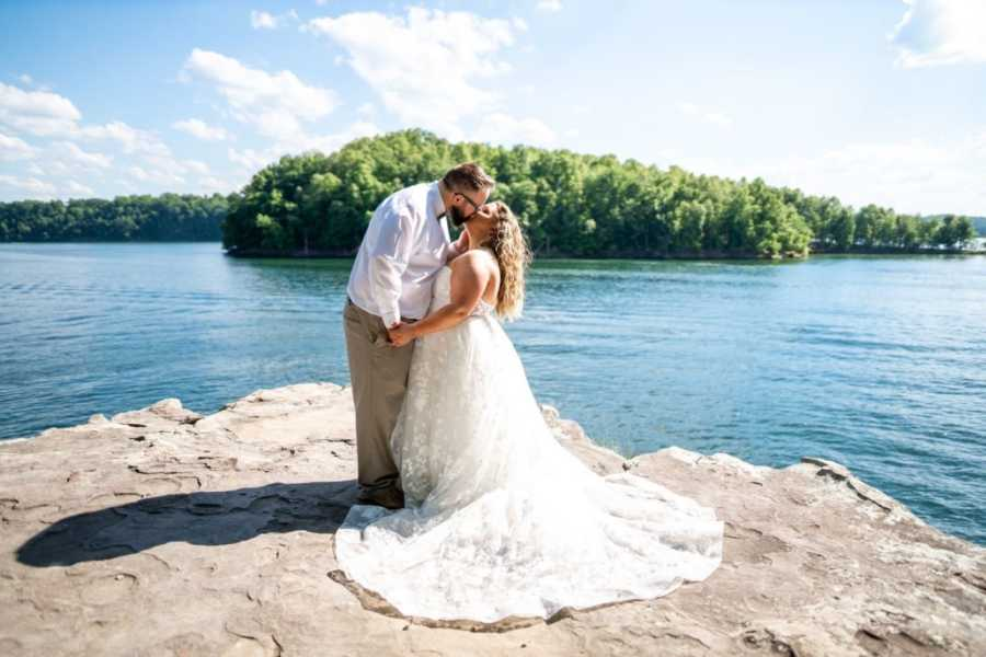 Couple celebrating their second wedding share a passionate smooch while overlooking a crystal blue lake