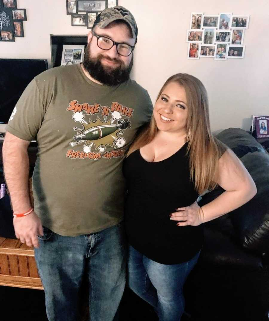 Couple take a photo together in their living room