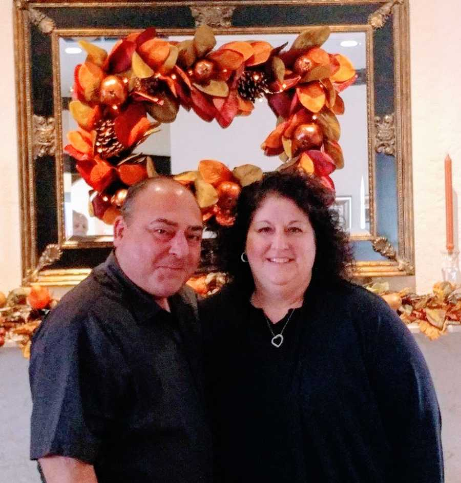 Married couple take photo together at Thanksgiving dinner with fall-themed decorations behind them