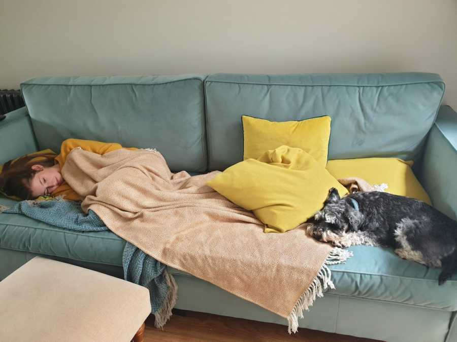 young girl laying on the couch with a dog