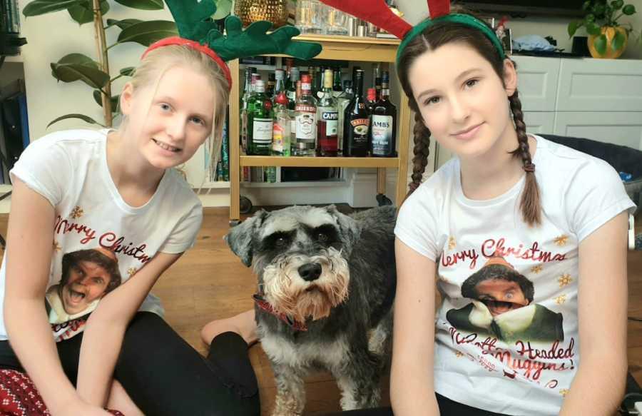 sisters in reindeer antlers with dog