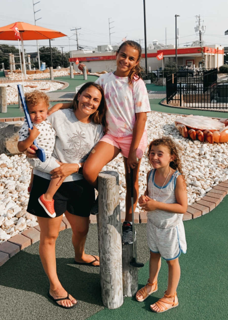family standing in a mini golf course