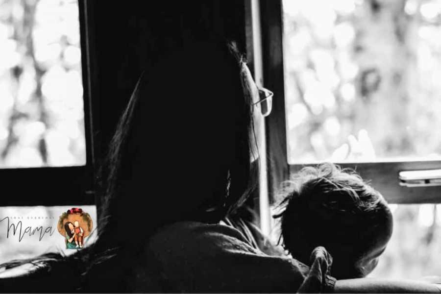 Woman stares out the window while holding her child and reflecting on overcoming her childhood trauma