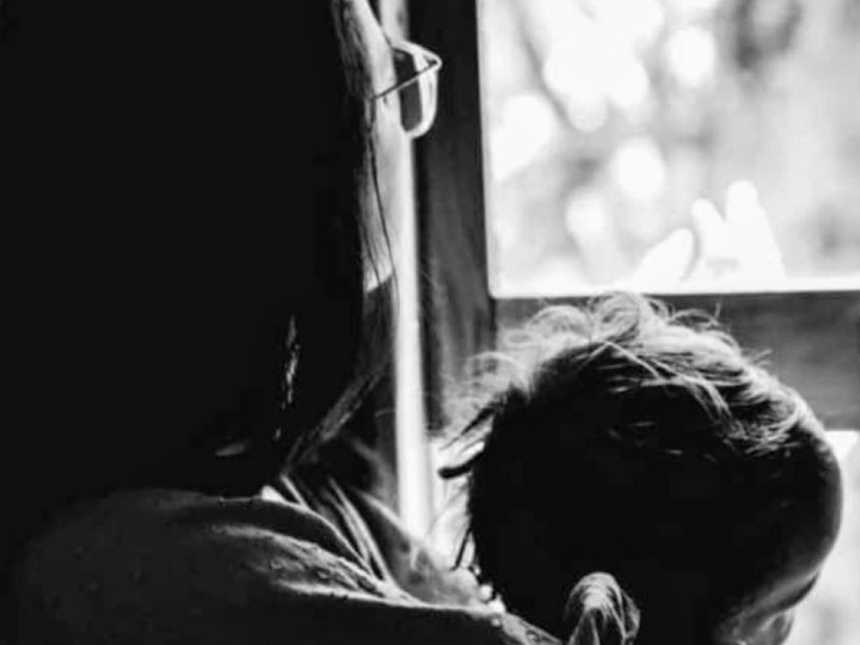 Mom holds her child while staring out the window in her living room