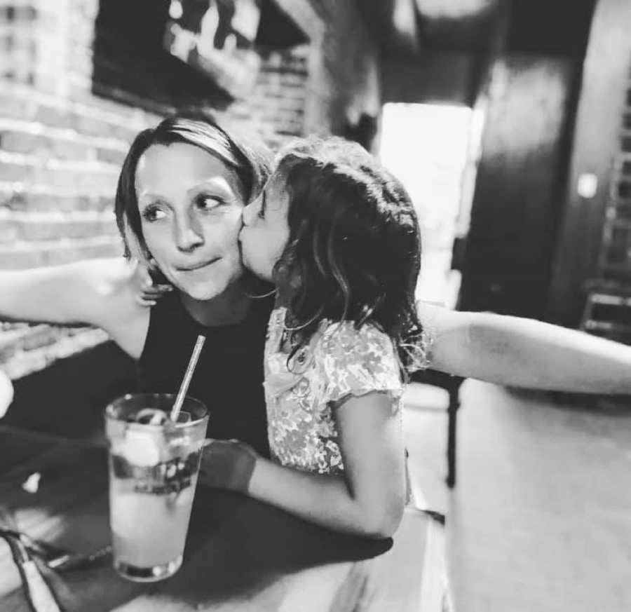 Mom and daughter share sweet moment while out at a restaurant
