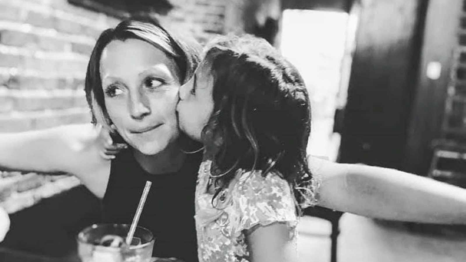 Mom takes a photo with her daughter while she kisses her on the cheek