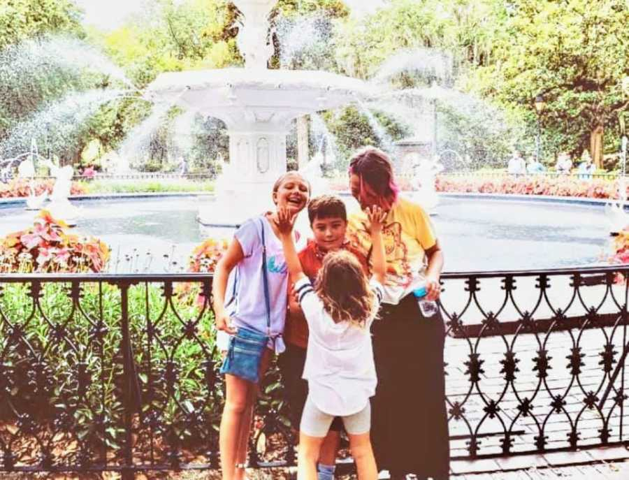 Mom smiles down at her three kids while posing for a photo on vacation in front of a fountain