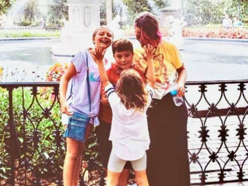 Mom takes a candid photo in front of a fountain with her three children