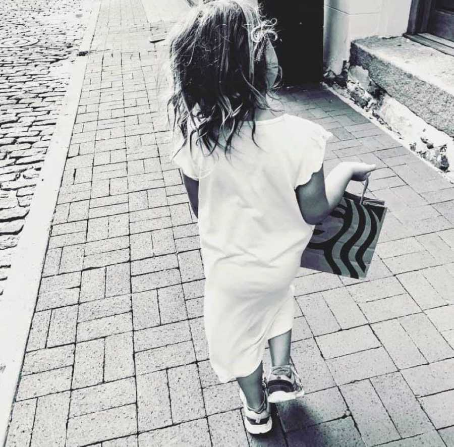 Mom of three snaps a photo of her youngest daughter walking down the sidewalk in a long dress