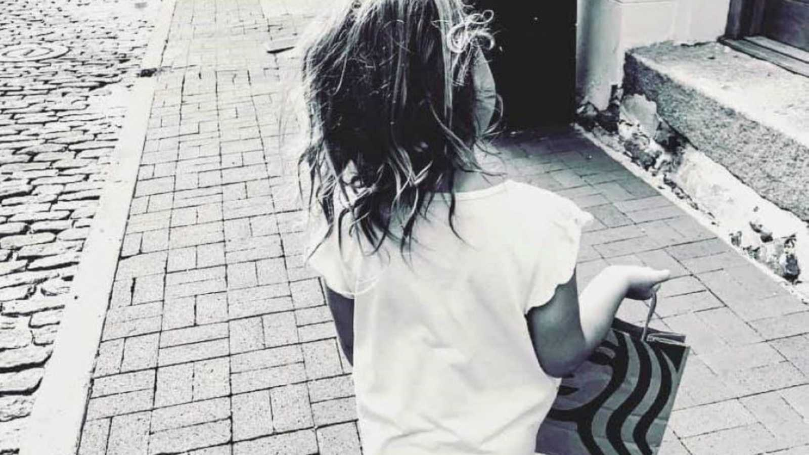 Mom snaps a photo of her daughter walking down the sidewalk while carrying a Starbucks bag