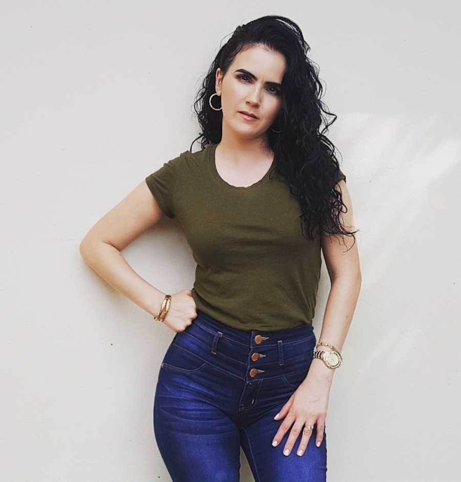 woman confidently smiling in olive top and jeans, hand on hip