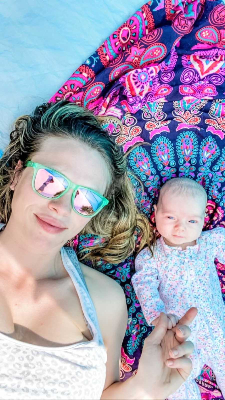 Mom and newborn daughter enjoy a sunny day together while laying out on some blankets