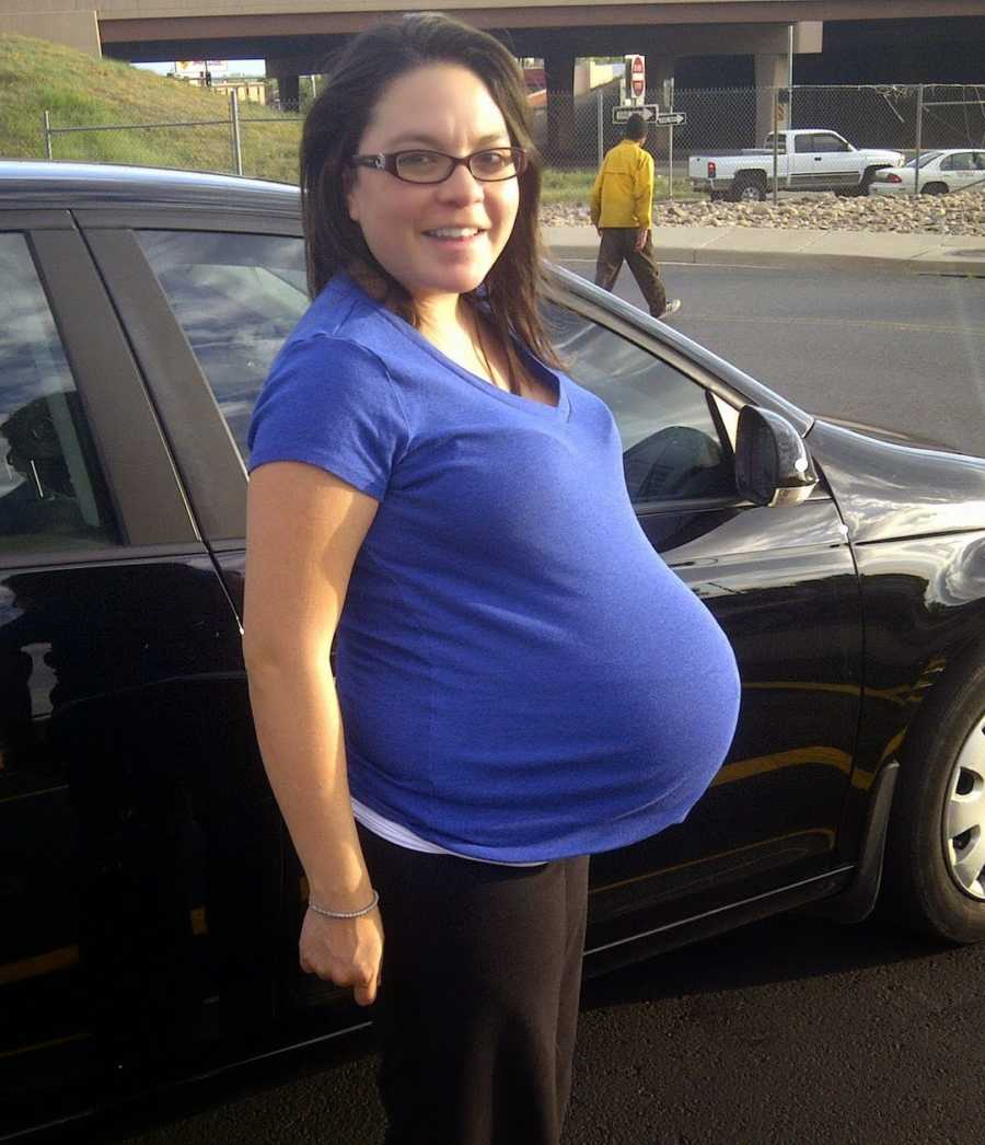 maternity photo of woman smiling in blue shirt