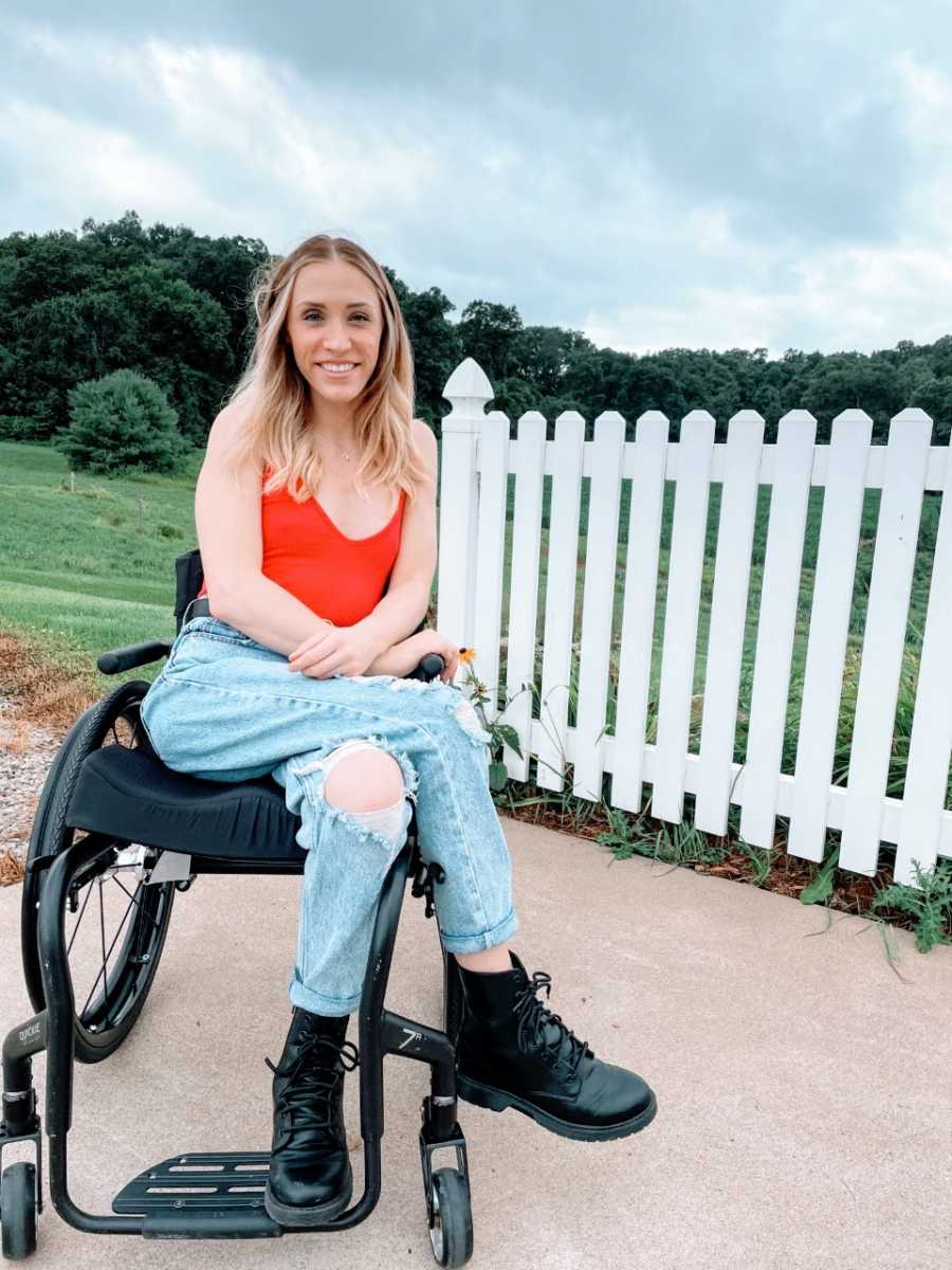Woman smiles big for a photo while sitting in her wheelchair