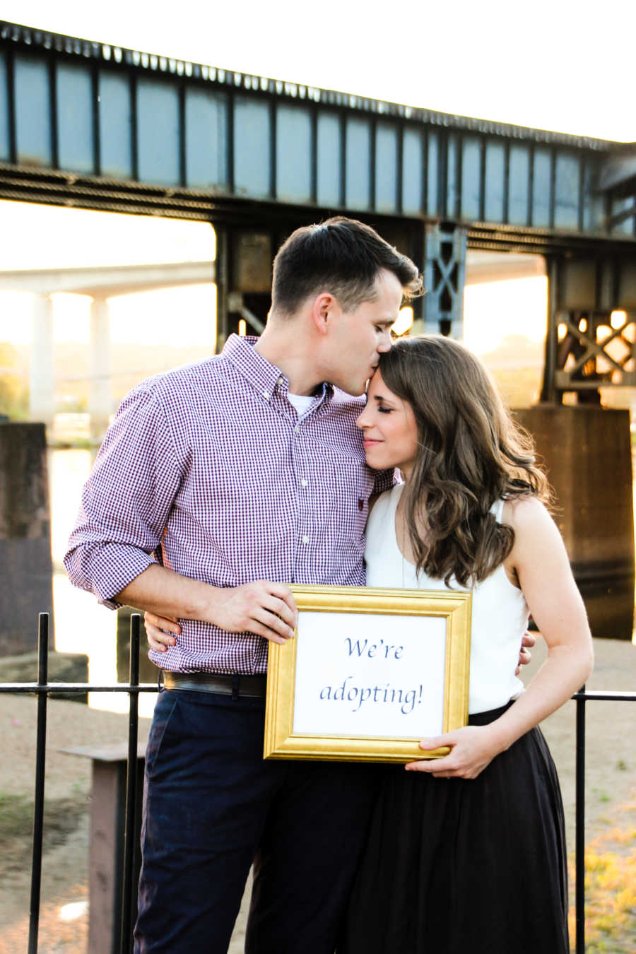 """couple holding """"we're adopting"""" sign"""