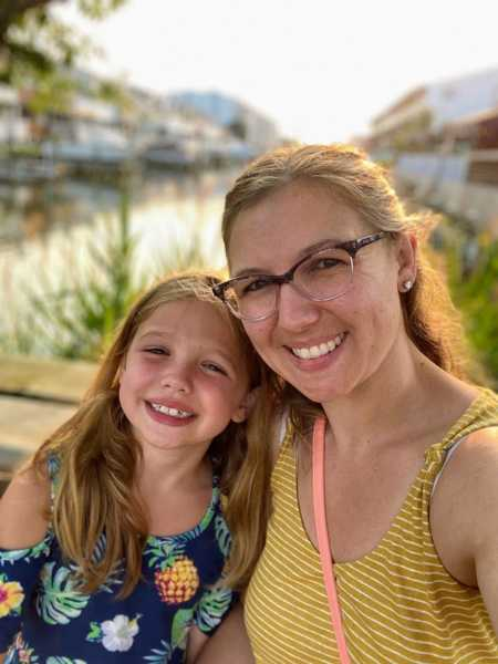 Mom takes selfie with diabetic daughter in front of beautiful waterfront scenery