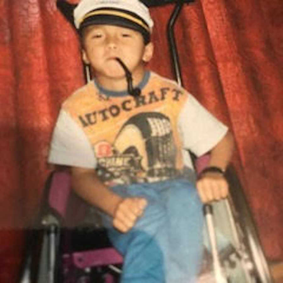young boy in wheelchair with toy pipe