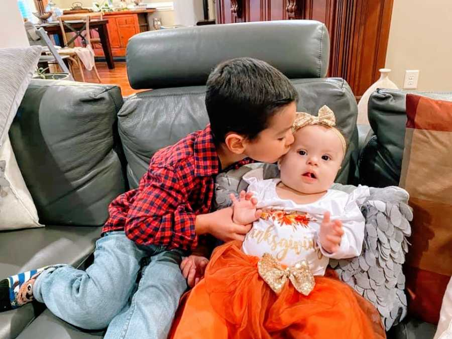 A little boy kisses his baby sister on the cheek