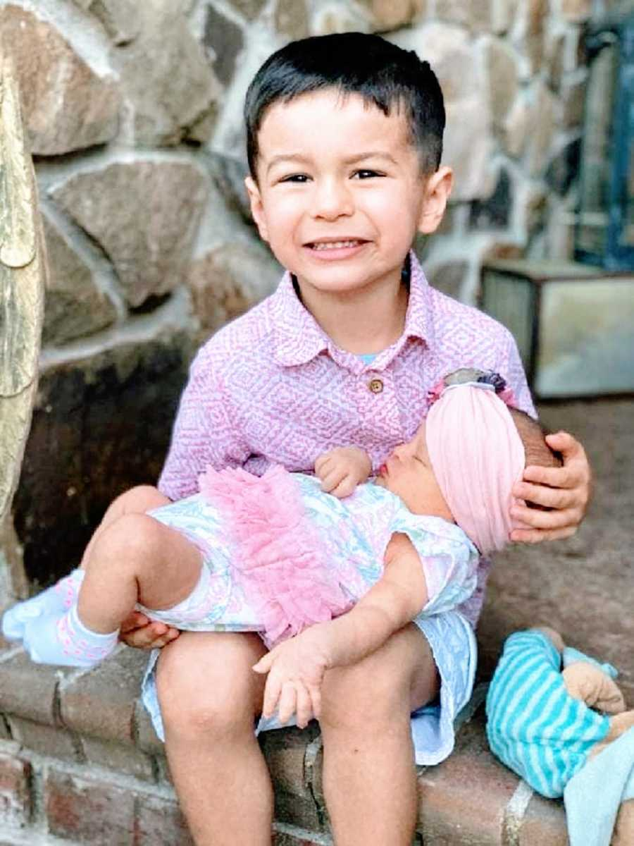 A little boy holds his baby sister on his lap