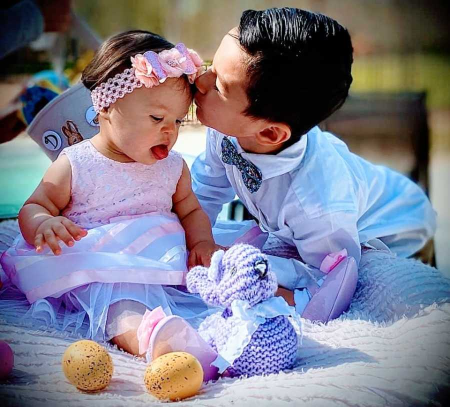 A little boy kisses his baby sister on the forehead