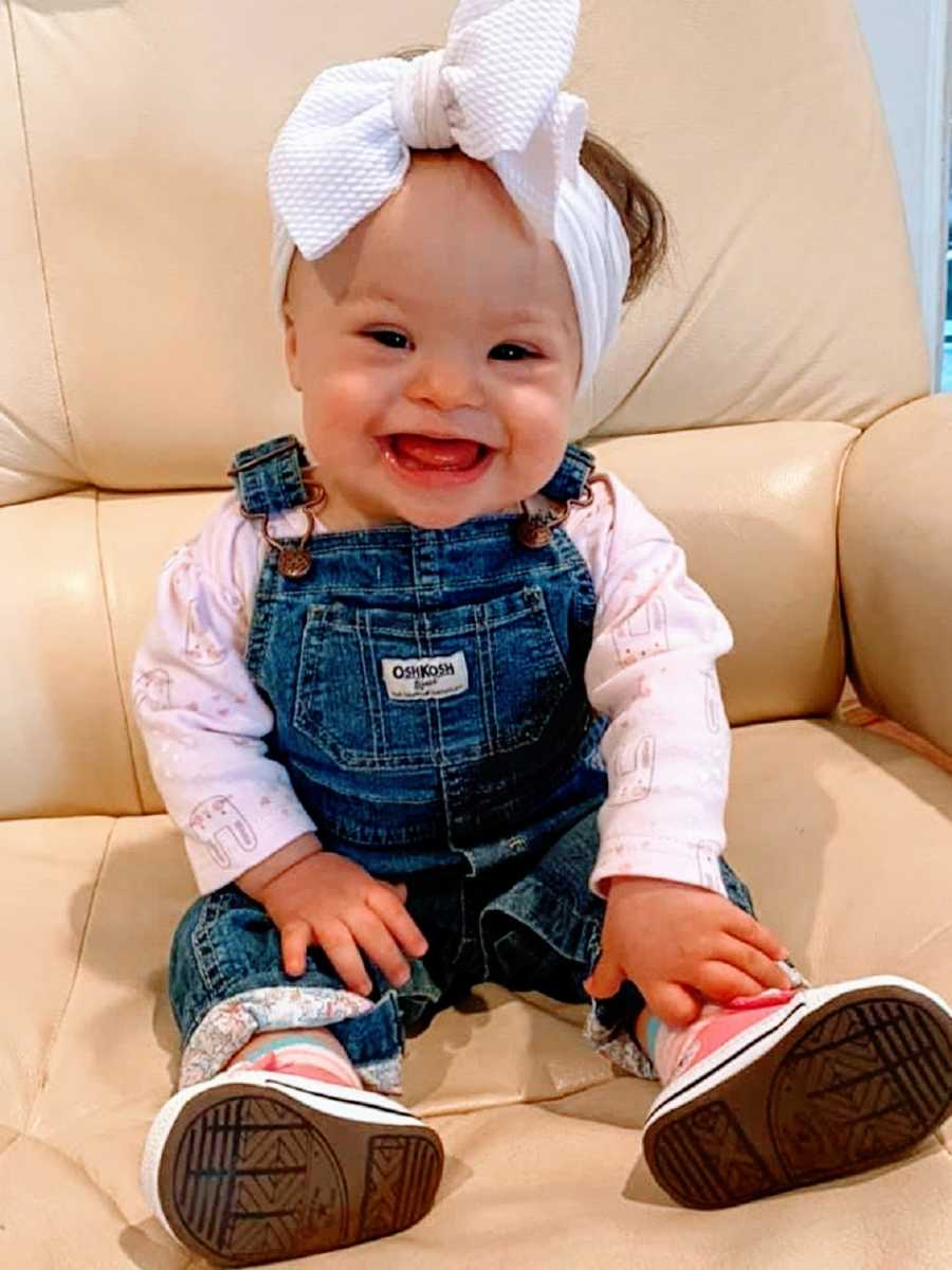 A baby girl wearing overalls and a bow on her head