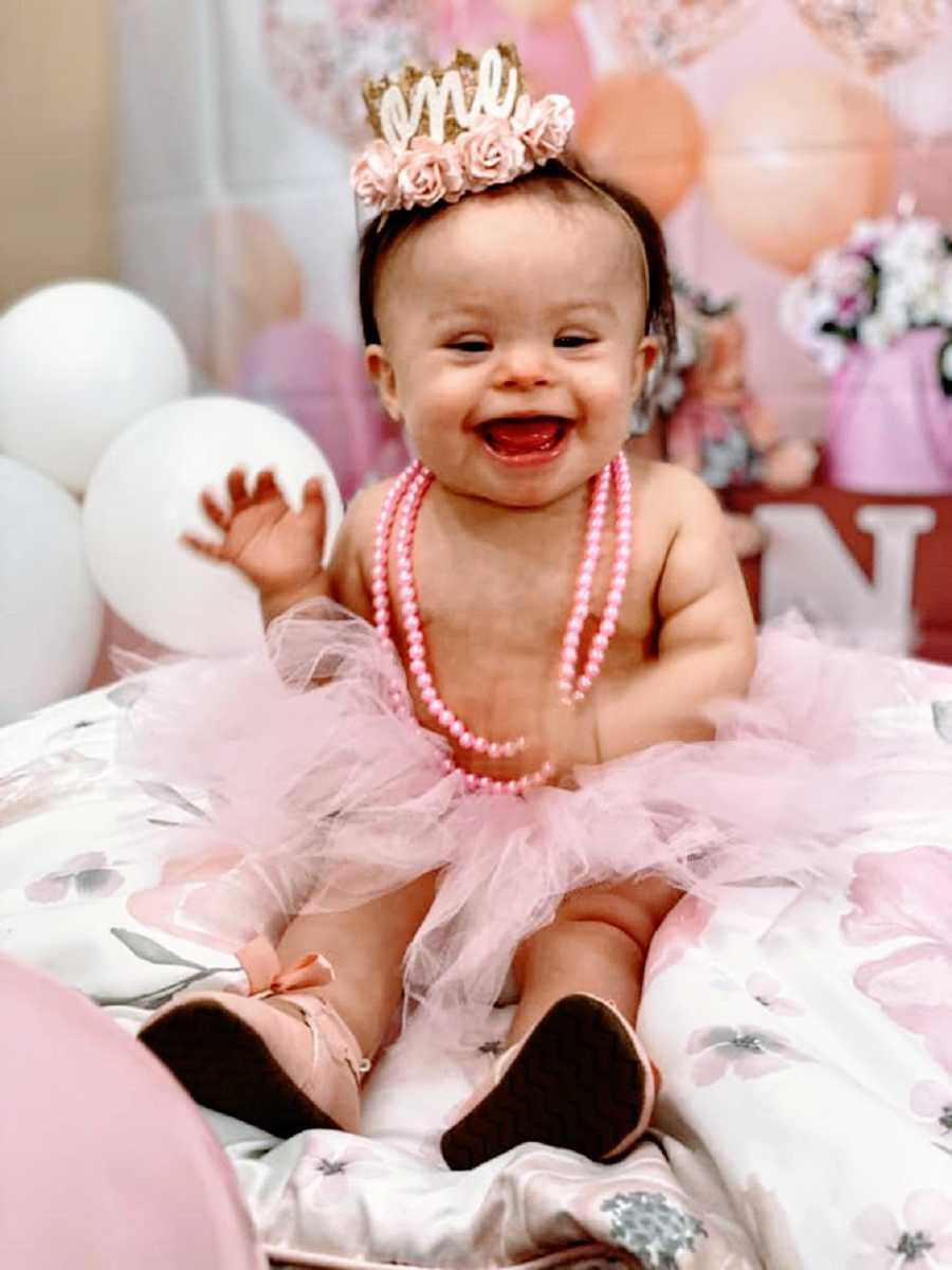 A little girl with down syndrome wearing a tutu