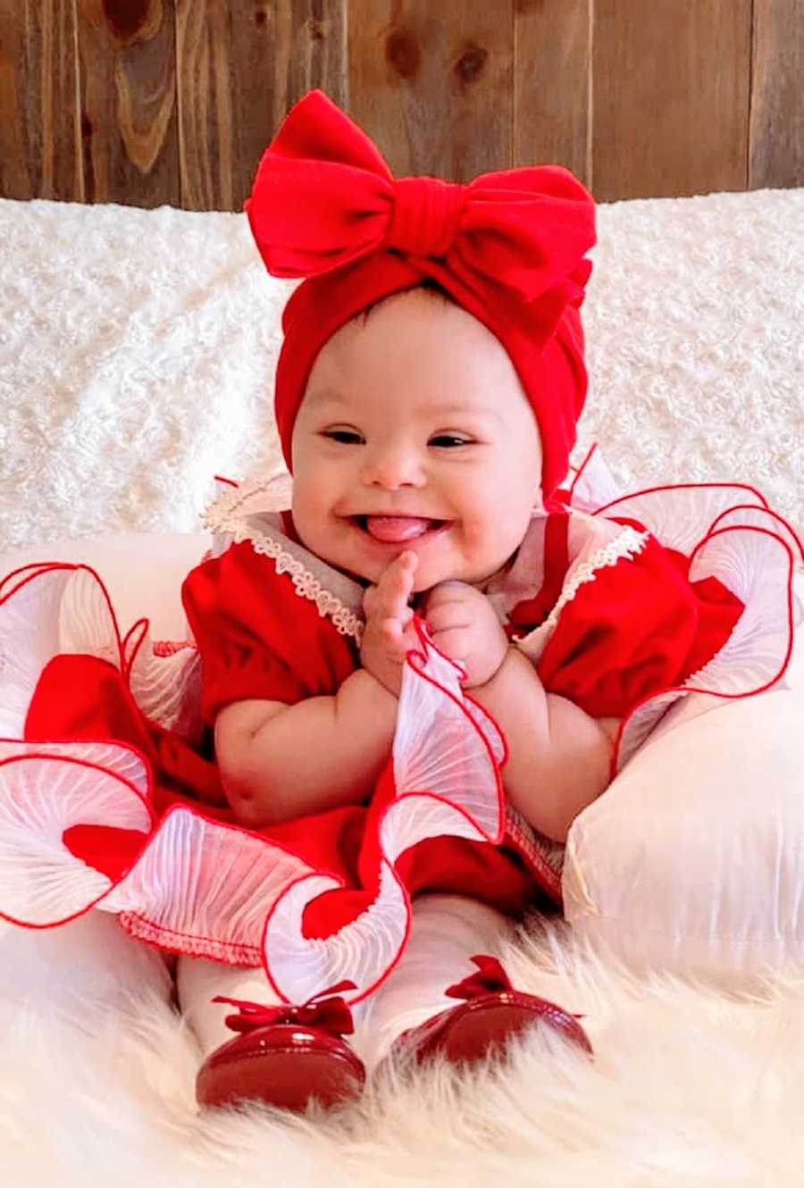 A little girl wearing a red dress and bow