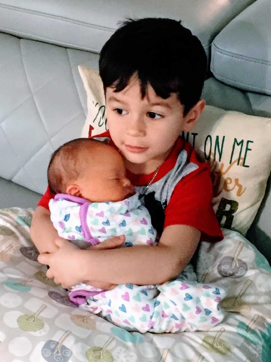 A little boy holds his baby sister
