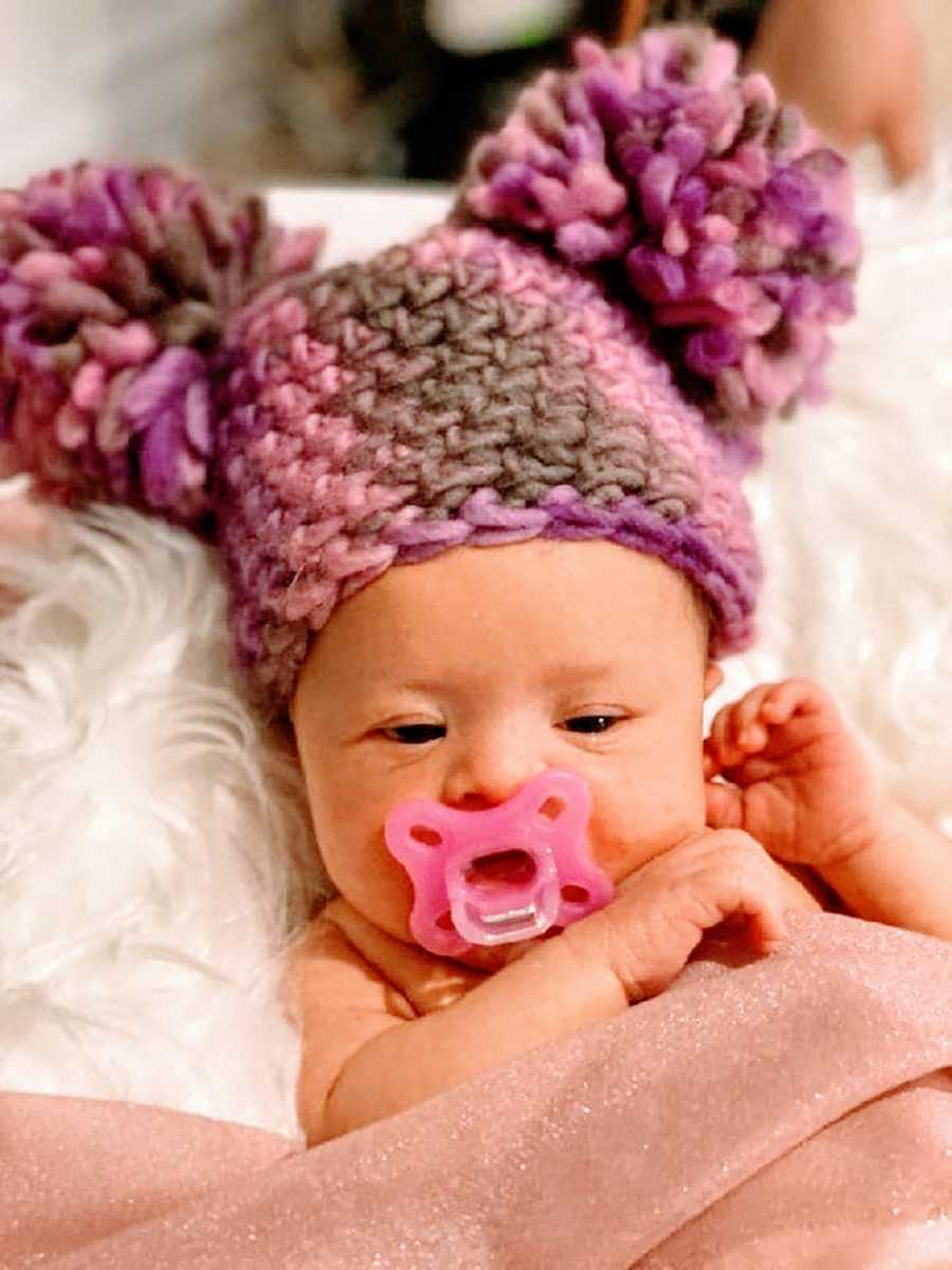 A little girl with a pacifier and a knit hat